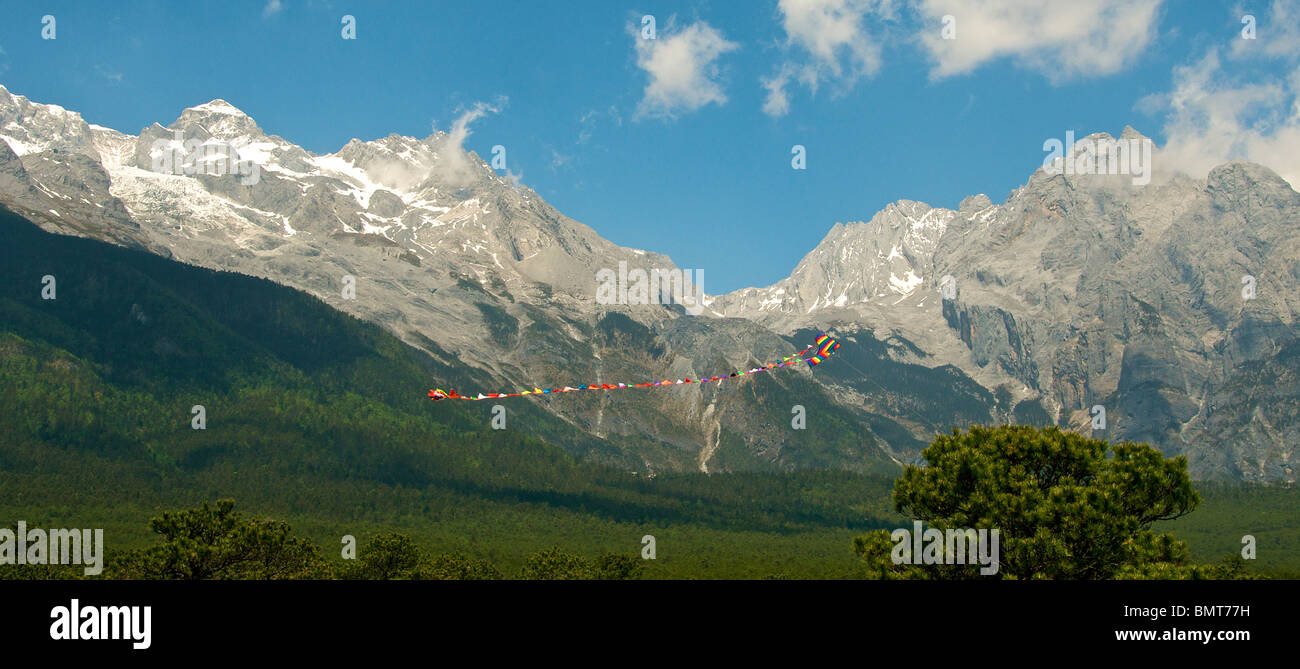 Kite flying with backdrop of summit of Yulong Xueshan (Jade Dragon) Mountain near Lijiang Yunnan China - Stock Image
