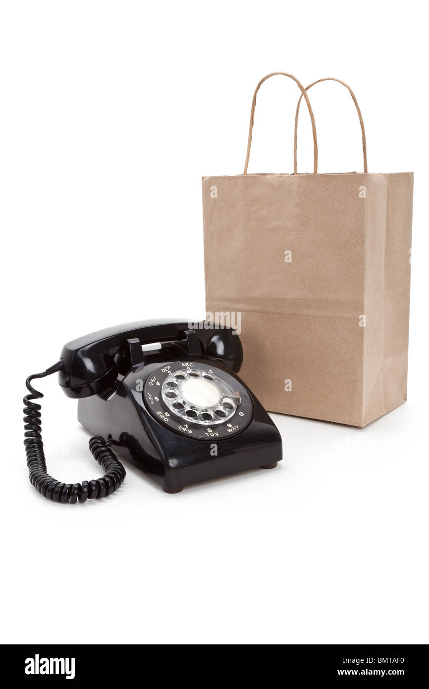 Brown paper shopping bag and telephone with white background Stock Photo