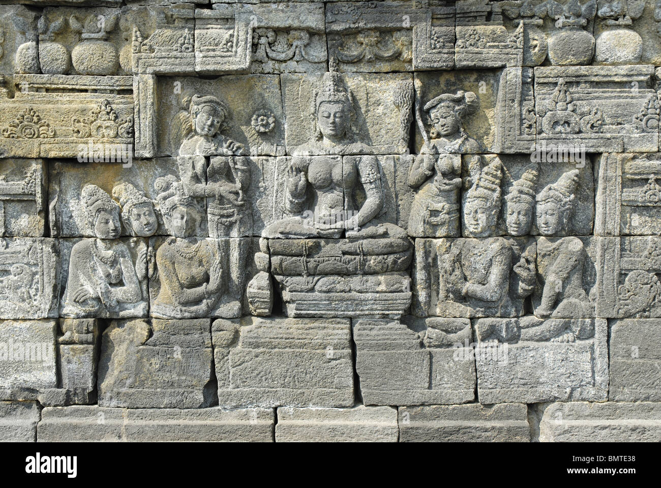 Indonesia Java Borobudur, Goddess seated on lotus throne with attendants and  Devotees, closer-view. - Stock Image