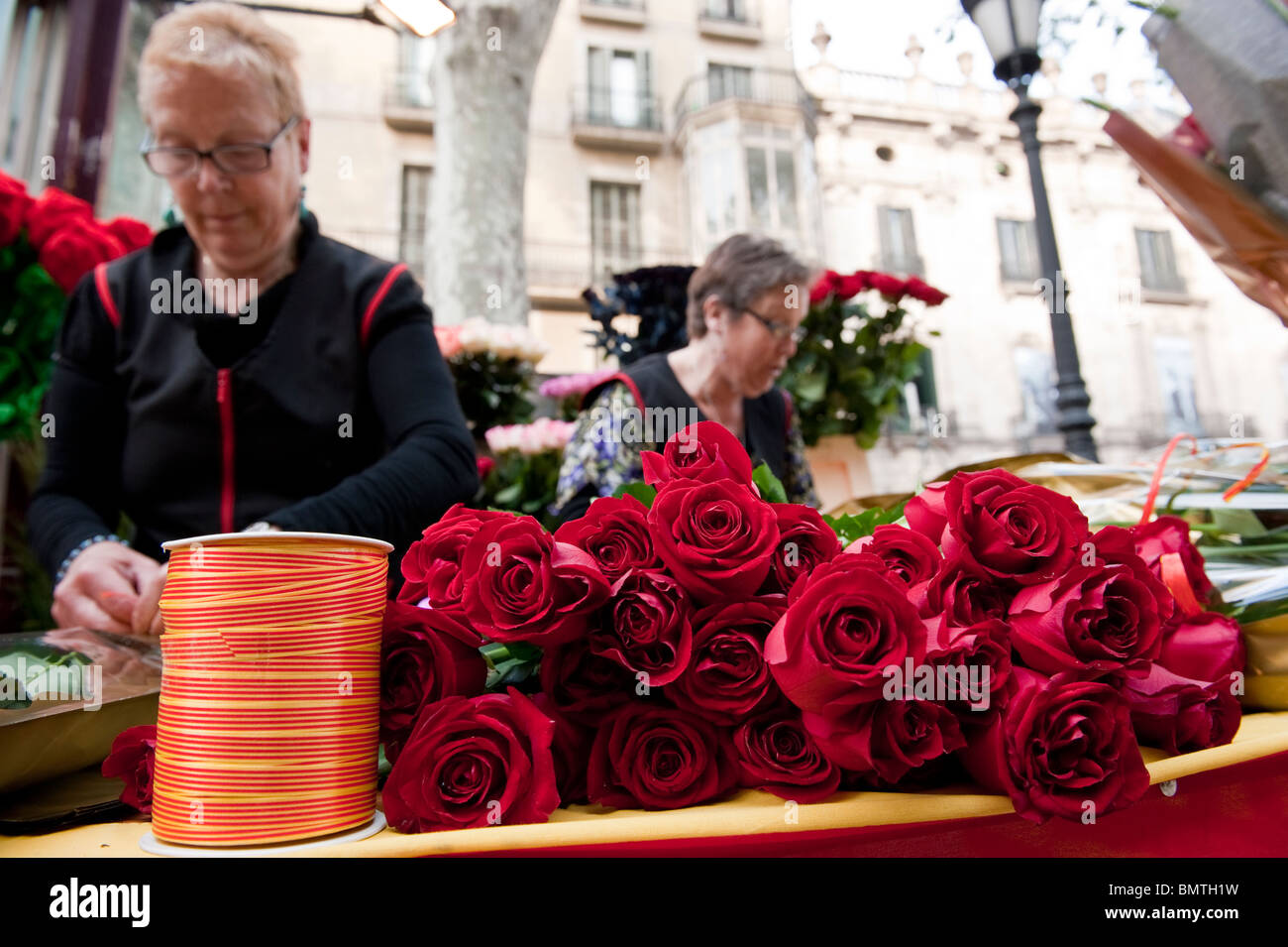 View of to woman selling roses in Las Ramblas for the traditional celebration of Sant Jordi. - Stock Image