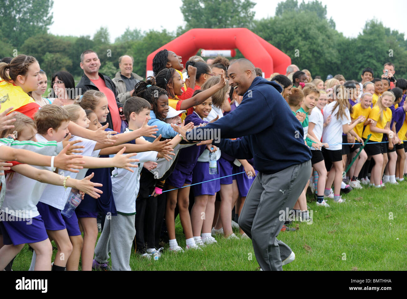 Colin Jackson doing a slap hands shake with hundreds of children taking part in the Tesco Great School run - Stock Image