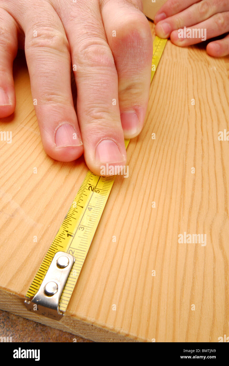 Carpenter is measuring wood, very close - Stock Image