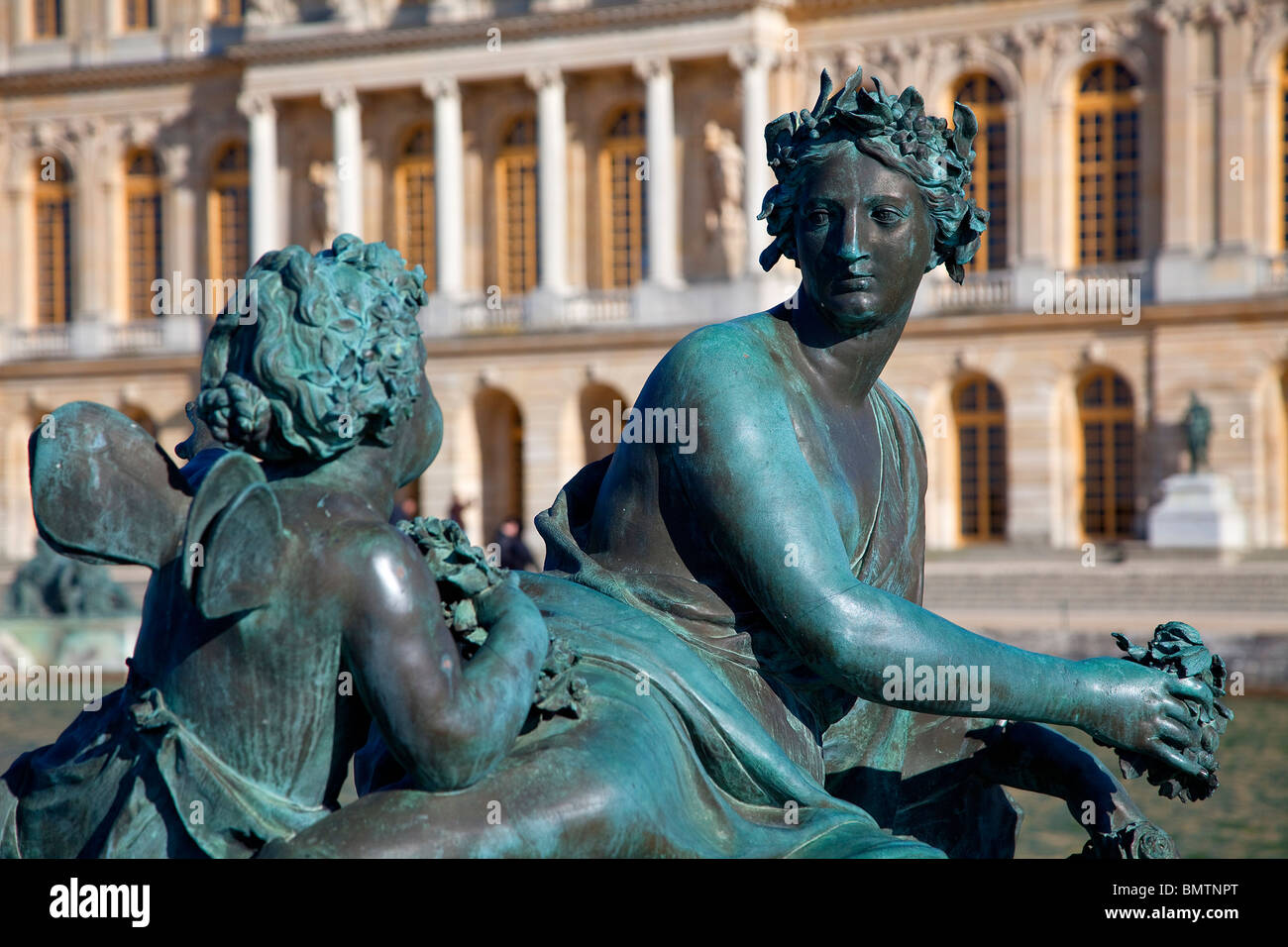 Bronze Sculpture at Fountain's Edge in Garden at Chateau de Versailles - Stock Image