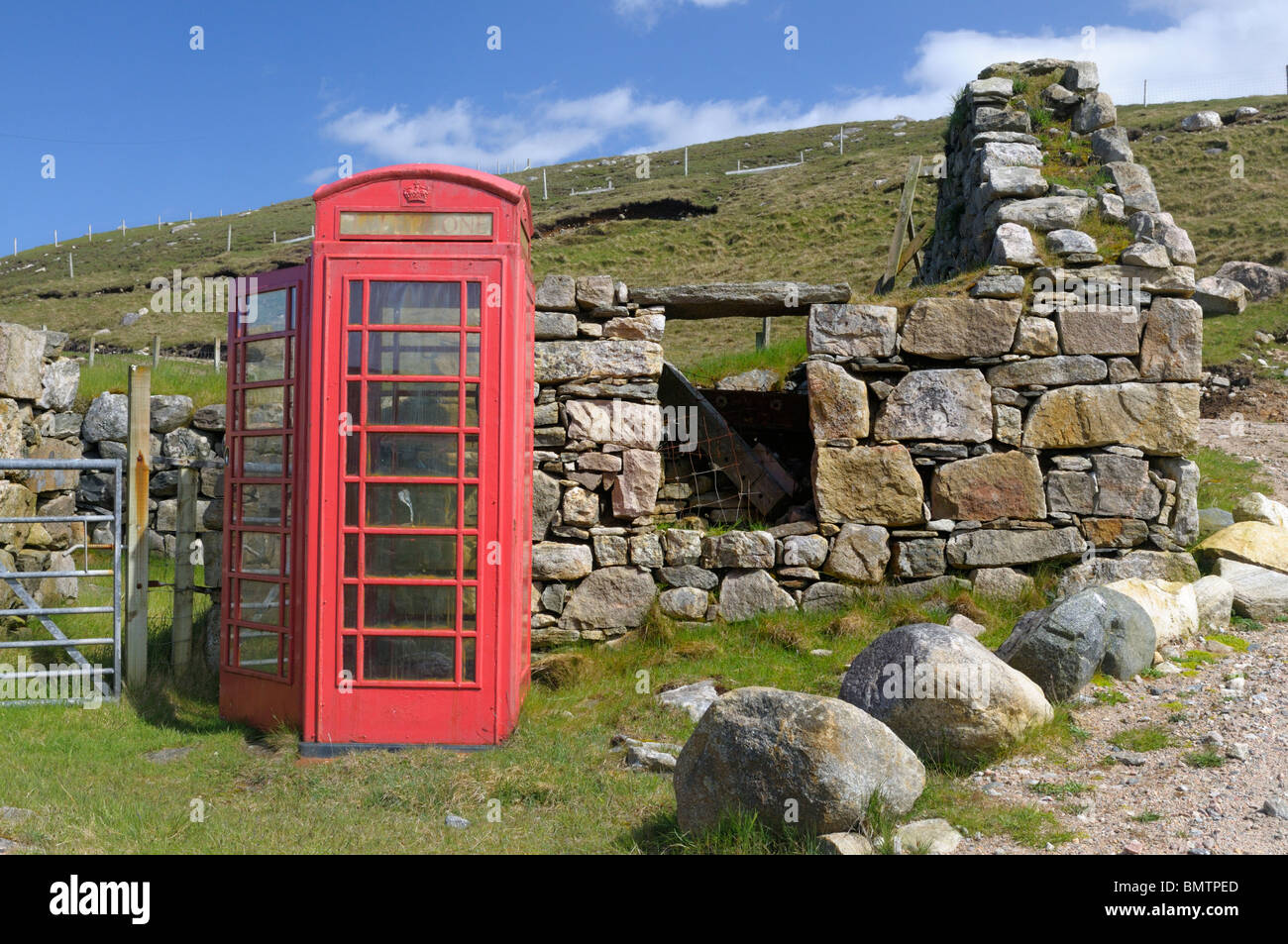 Old style red UK phone box next to a derelict croft house - Stock Image