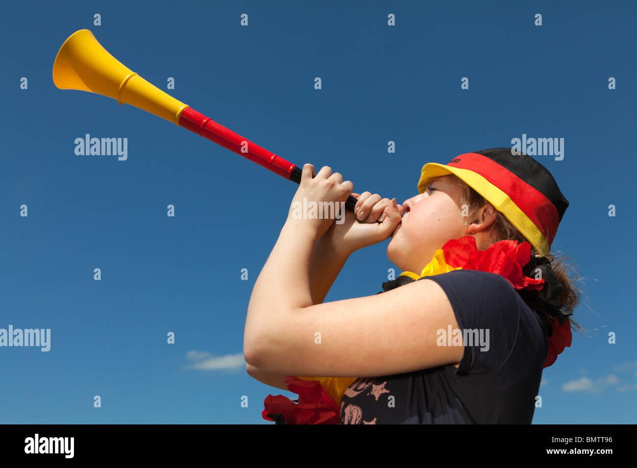 Female soccer fan blows vuvuzela - Stock Image