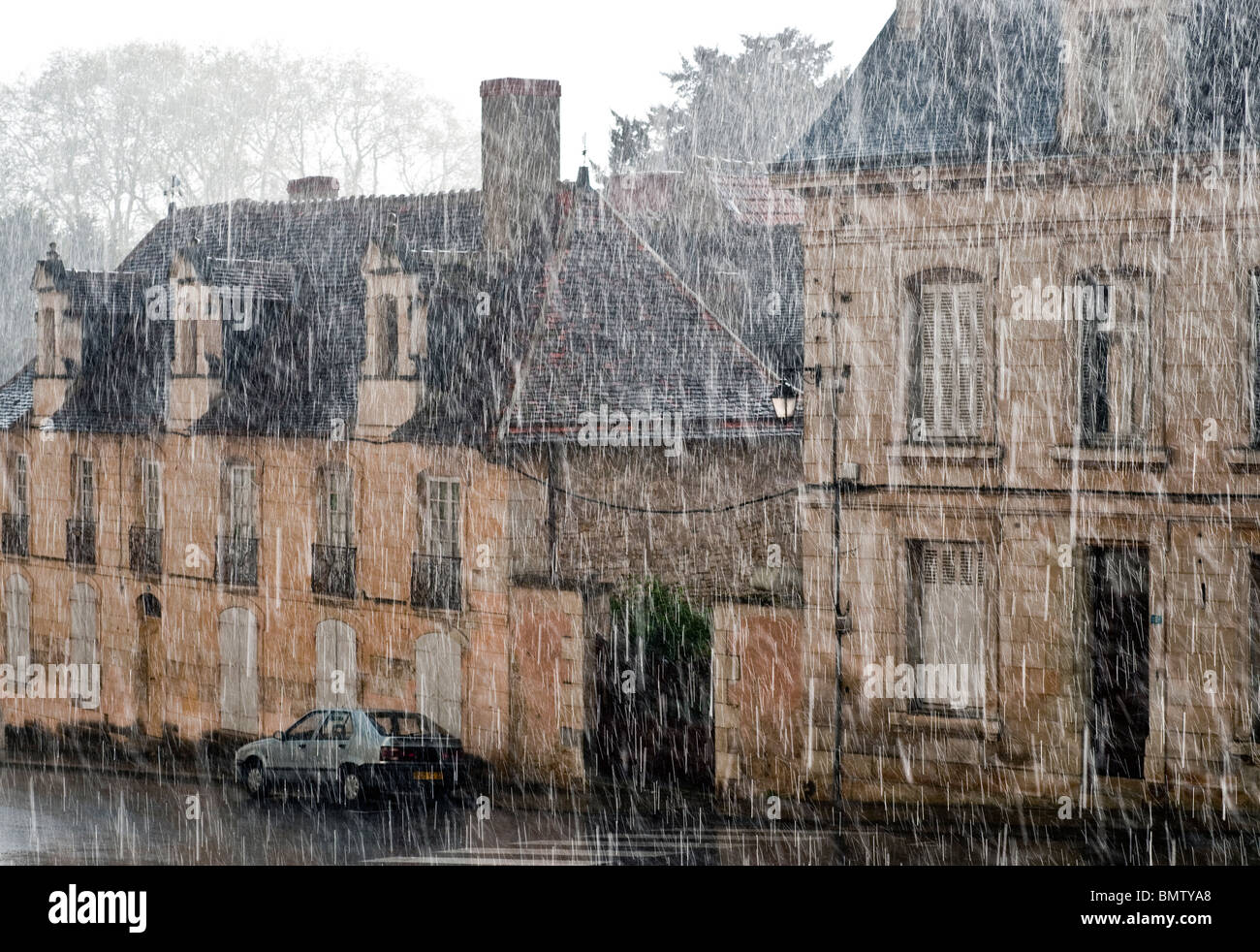 Torrential rainstorm in old town centre - France. - Stock Image