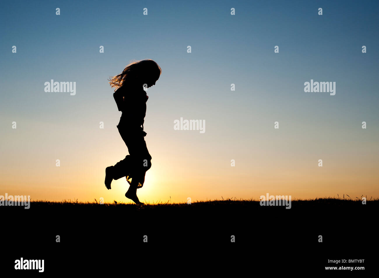 Young Girl energetically having fun and dancing around at sunset. Silhouette - Stock Image