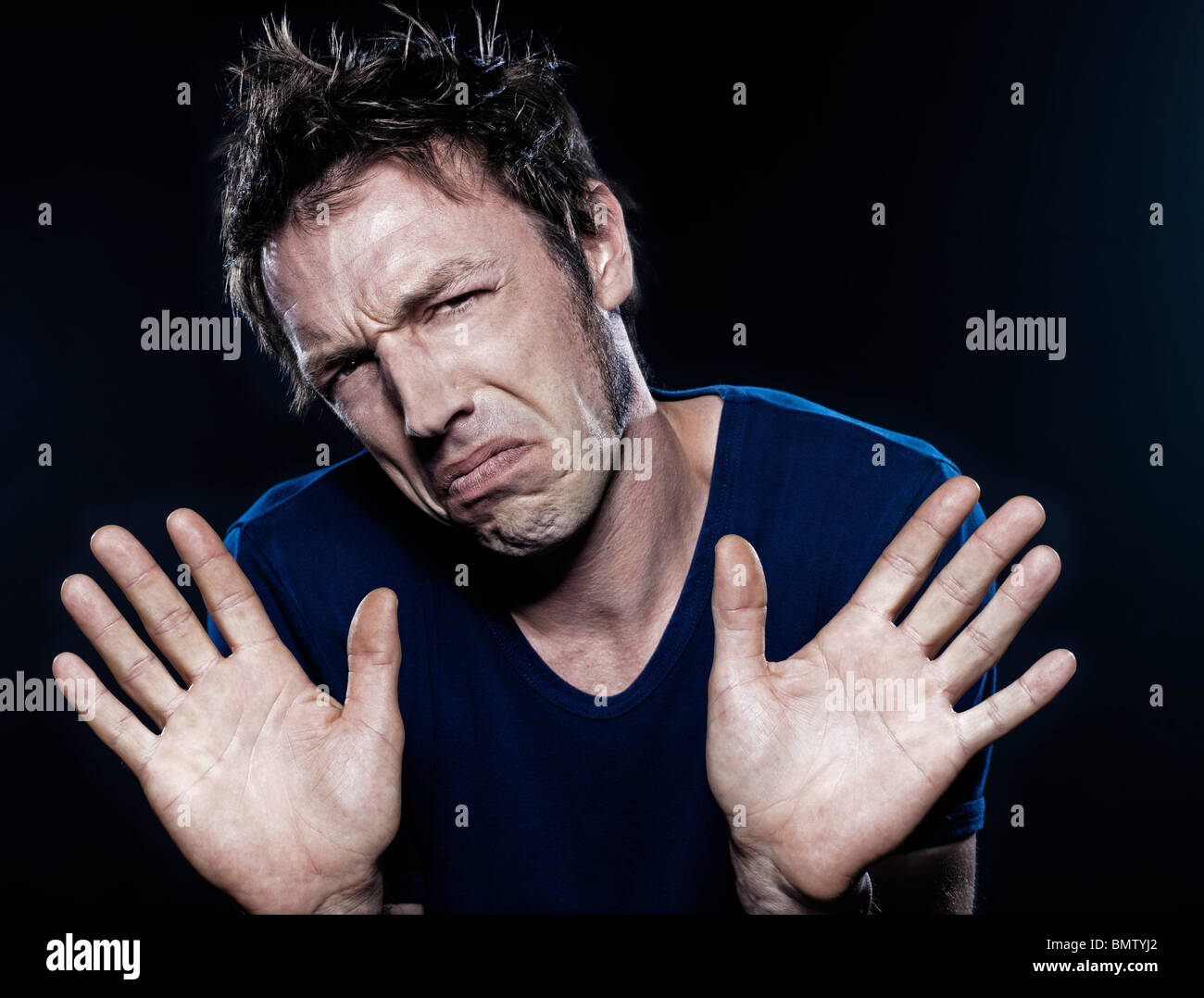 studio portrait on black background of a funny expressive caucasian man frowning refusal deny - Stock Image