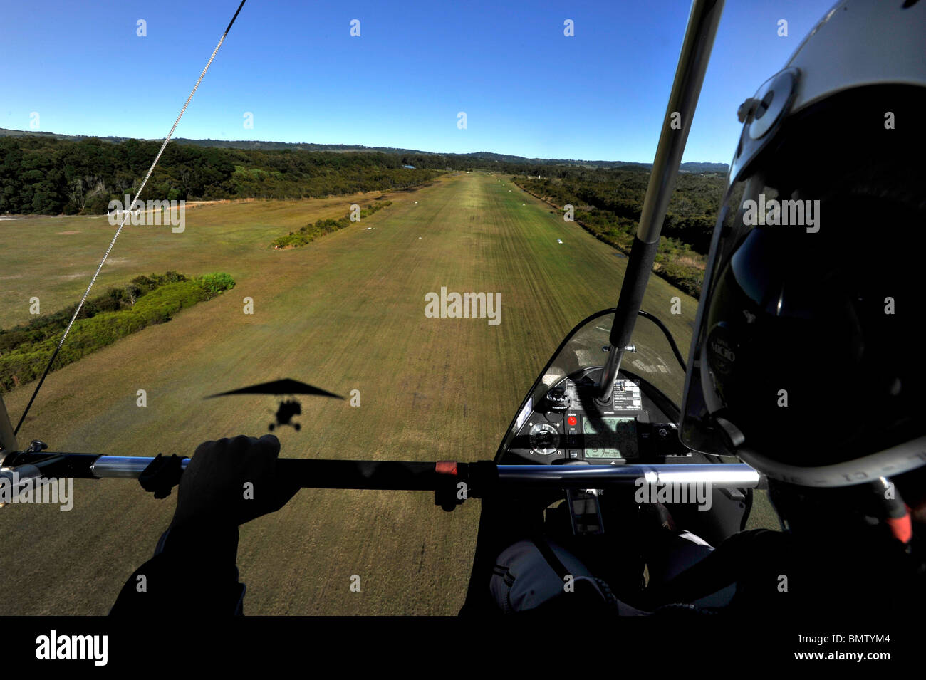 A microlight aircraft approaches a runway - Stock Image