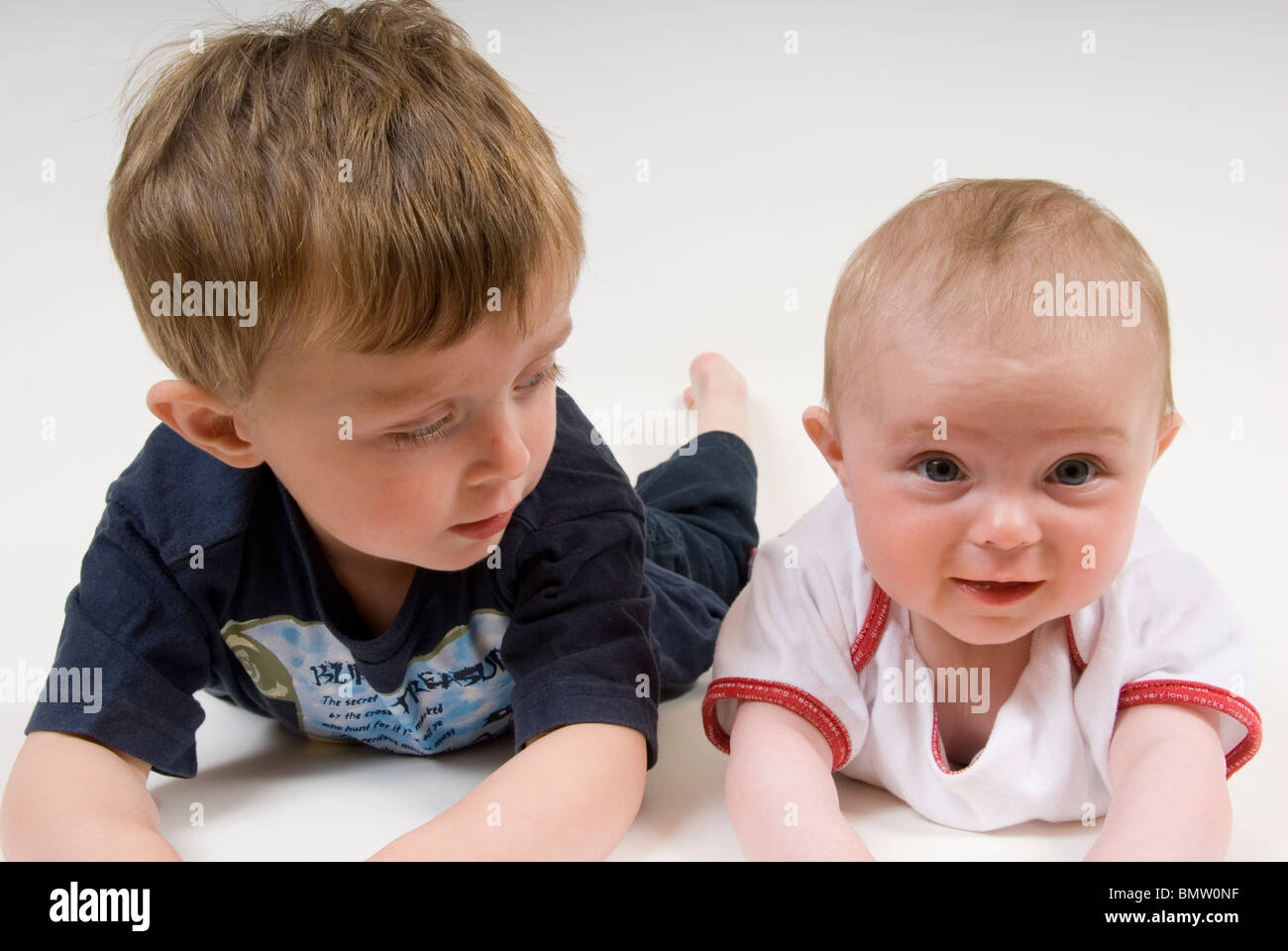 Portrait of Little Boy and with Baby Sister Lying on Tummies, Isolated on White - Stock Image