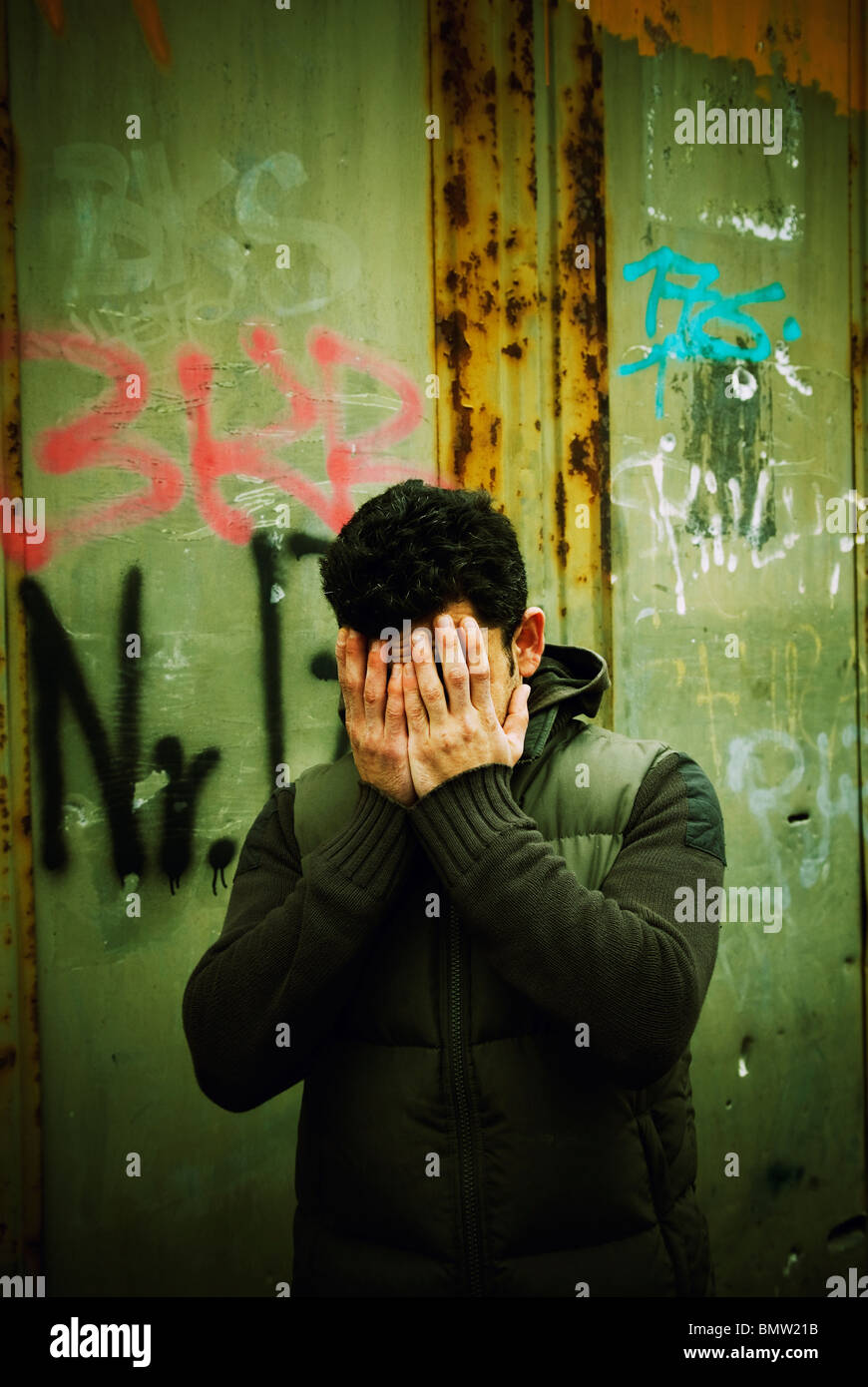 Man hiding face in hands outdoors Berlin Germany - Stock Image