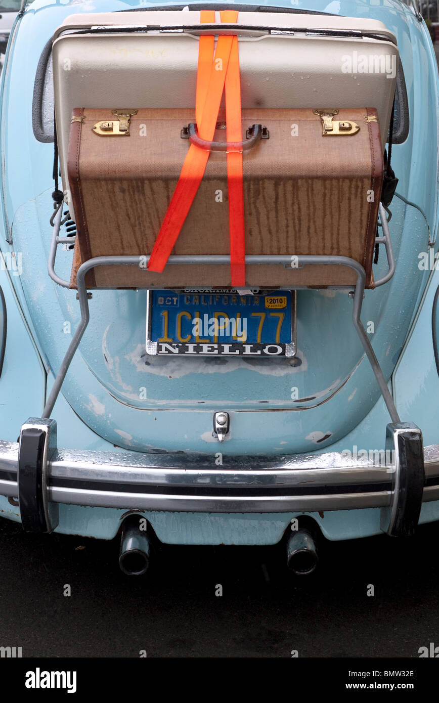 Luggage on rack attached to 1960's automobile - Stock Image