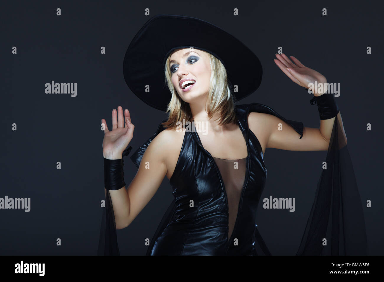 Smiling lady in the Halloween witch costume on a dark background - Stock Image