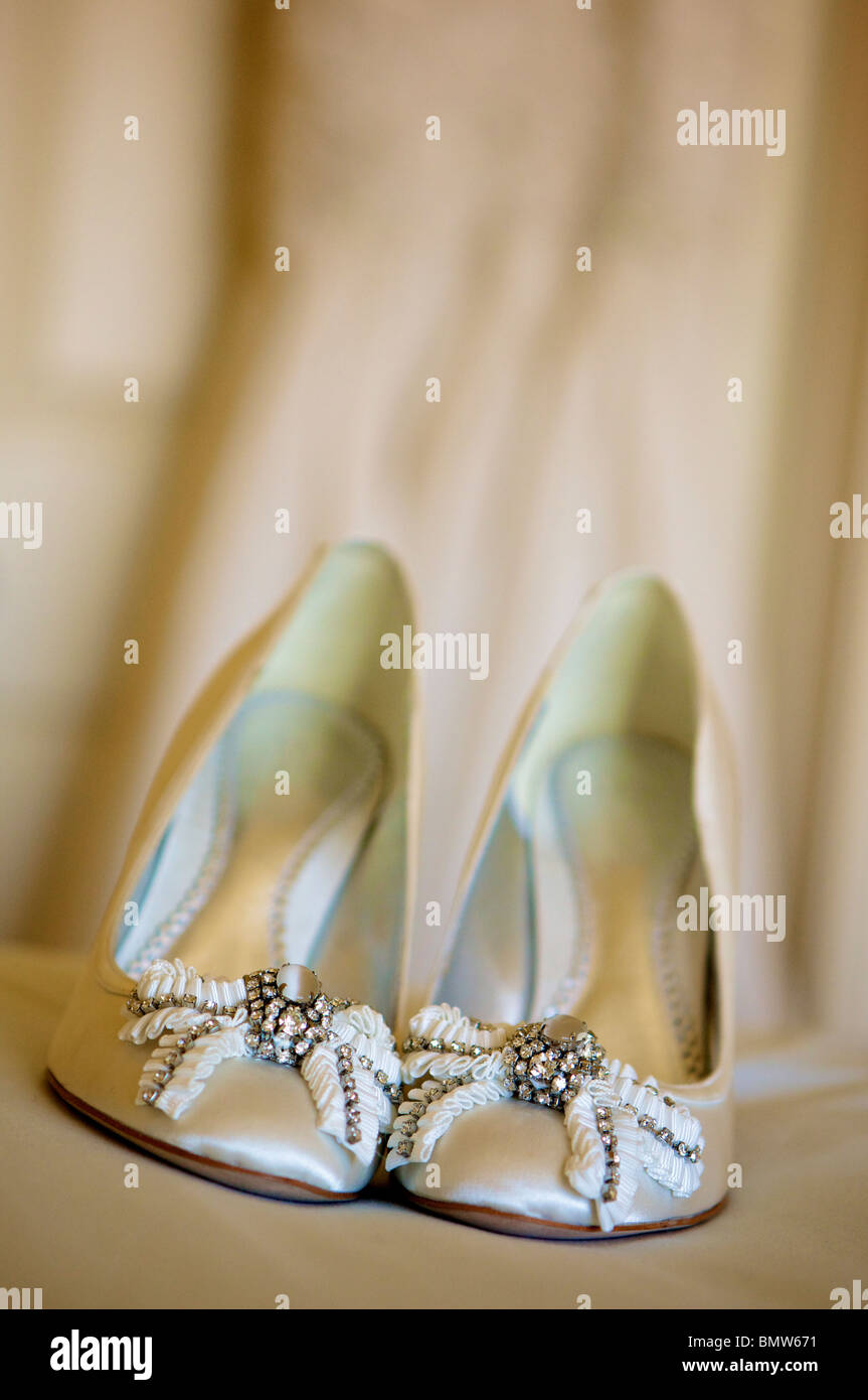 Brides wedding shoes on bed Stock Photo