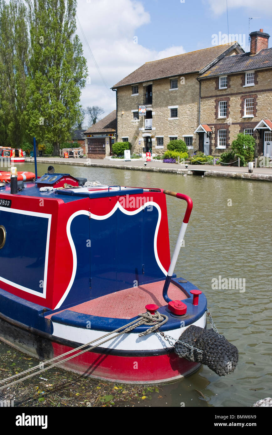 Red white and blue painted narrow boat on Grand Union canal at 'Stoke Bruerne' Northampton UK - Stock Image