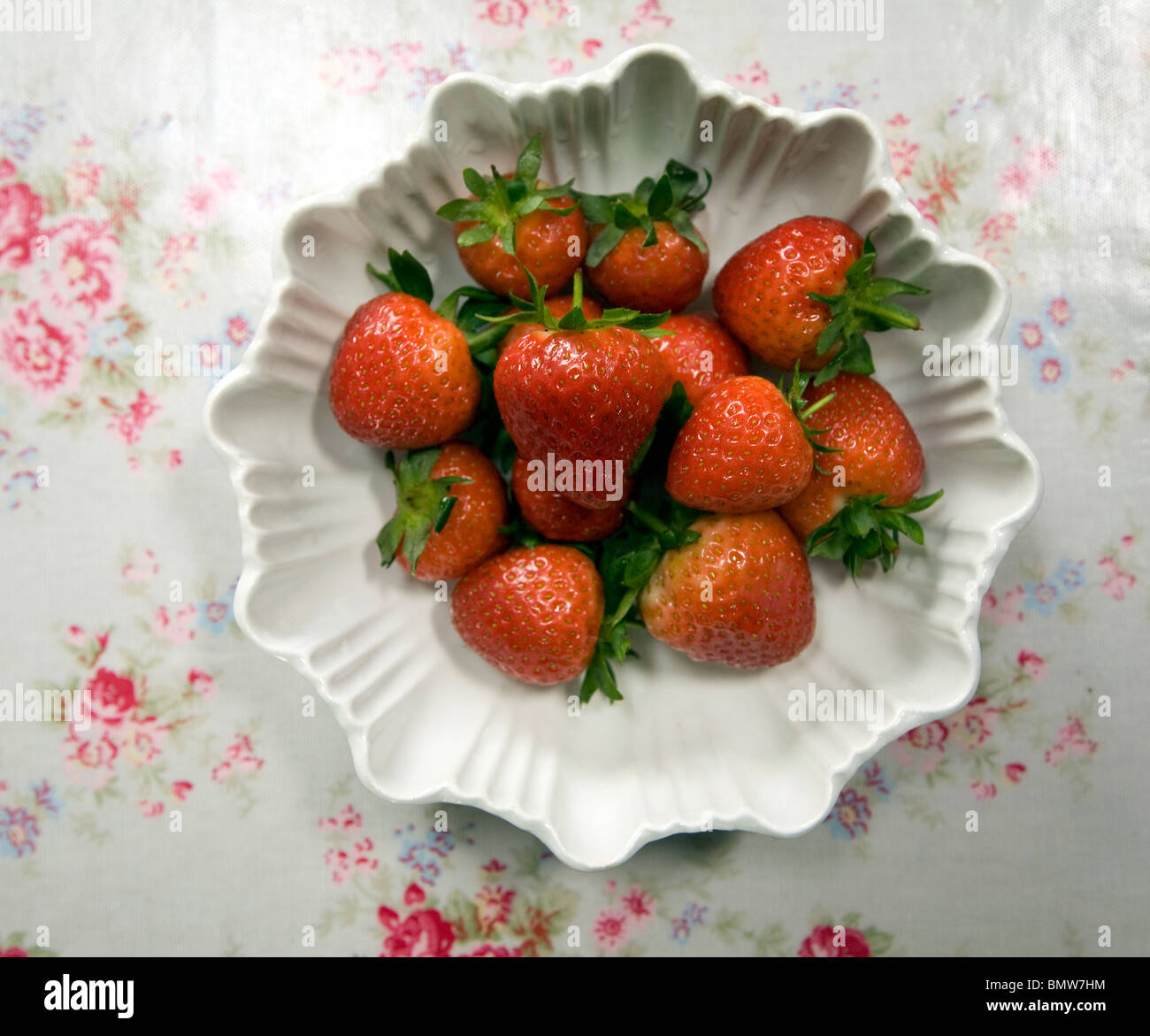 Looking down bowl strawberries floral tablecloth - Stock Image