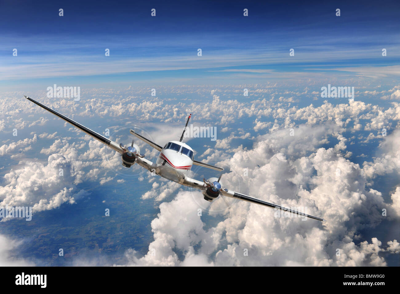 Airplane flying high above the clouds - Stock Image