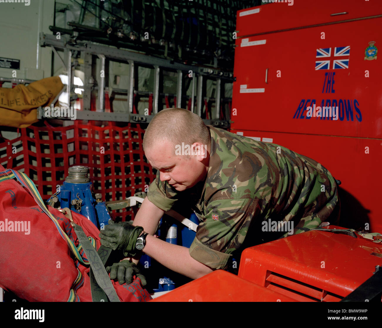Member of Red Arrows aerobatic team supervises loading of spares and personal effects into a C-130 Hercules for - Stock Image