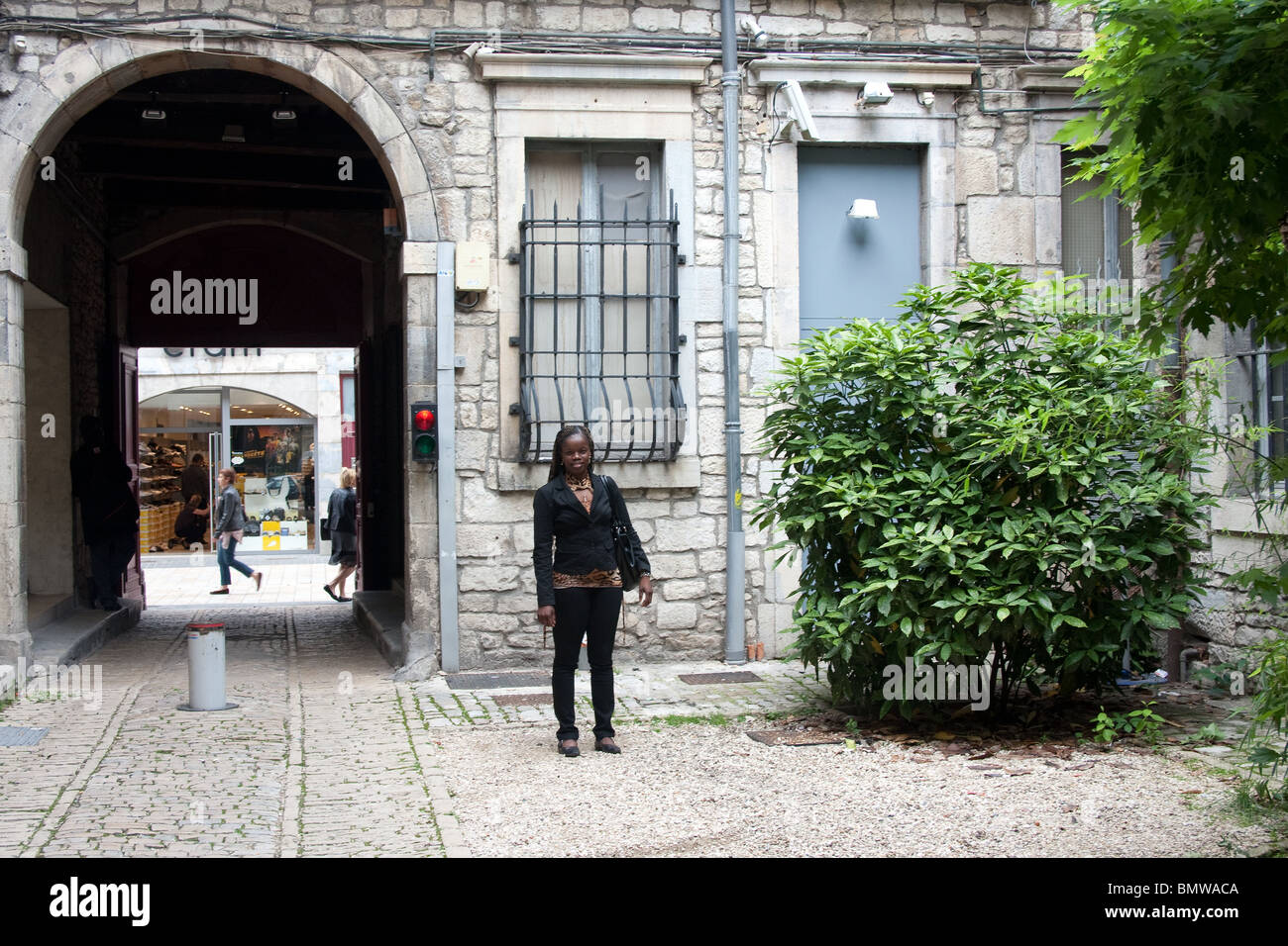 black afro Caribbean tourist posing courtyard arch - Stock Image