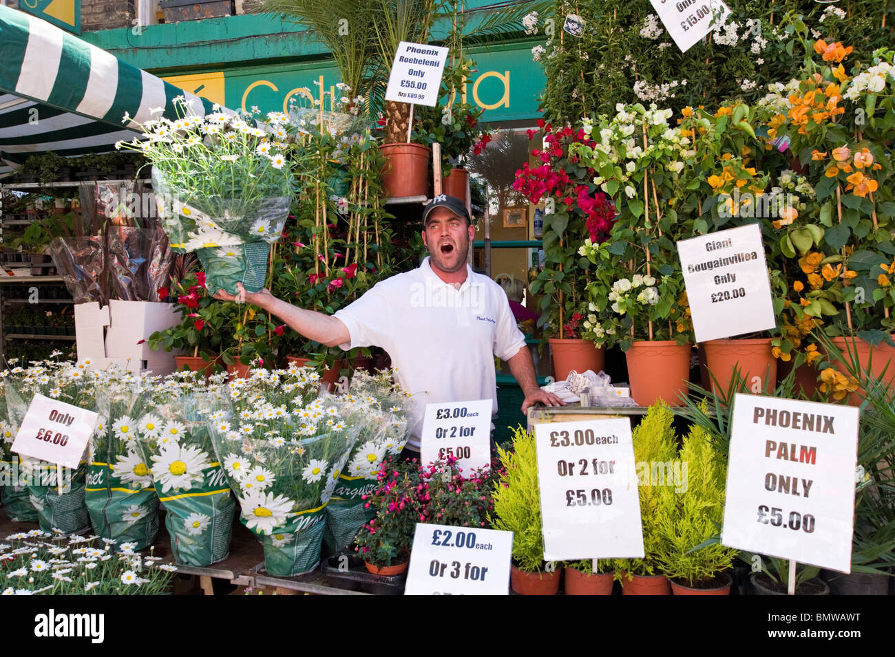 Street trader selling flowers at Columbia Road Flower Market, London, England, UK - Stock Image
