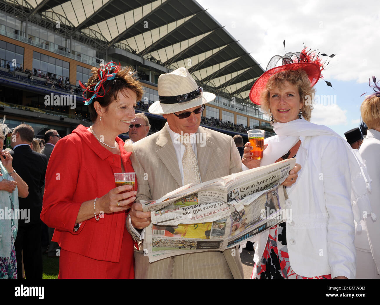 Royal Ascot  Horse racing male and female Racegoers look at the Racing Post to decide which horses to back - Stock Image