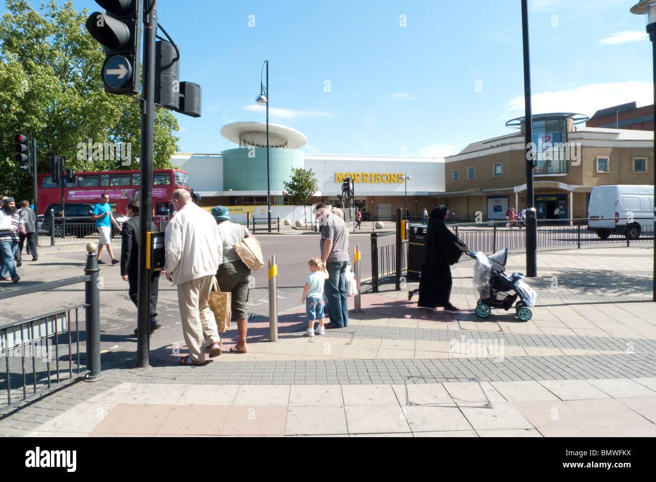 Pedestrians crossing street at traffic lights near Morrisons supermarket Stratford East London England UK - Stock Image