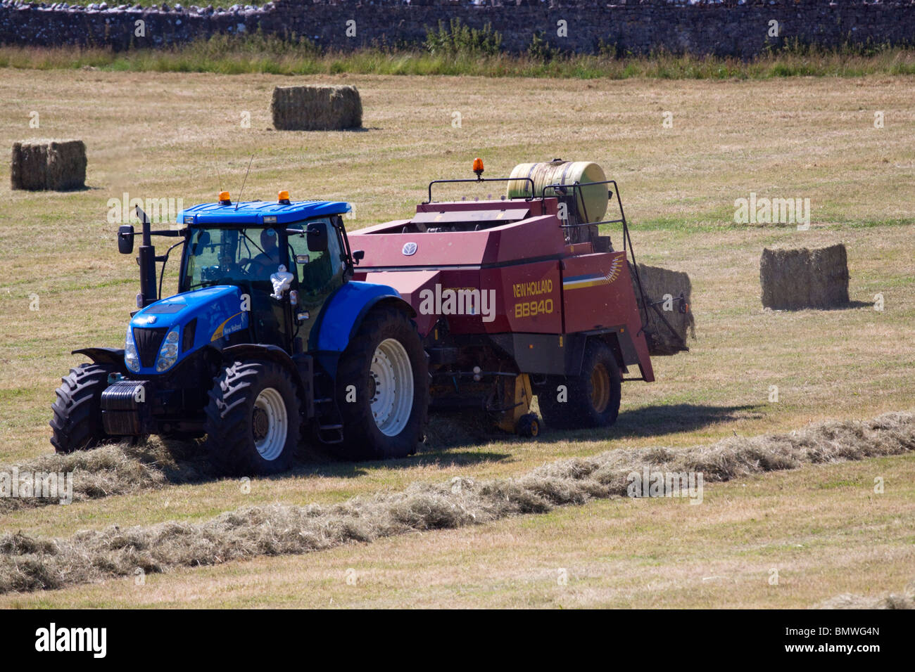 Blue Farm tractor and hay baler collecting hay on windrows