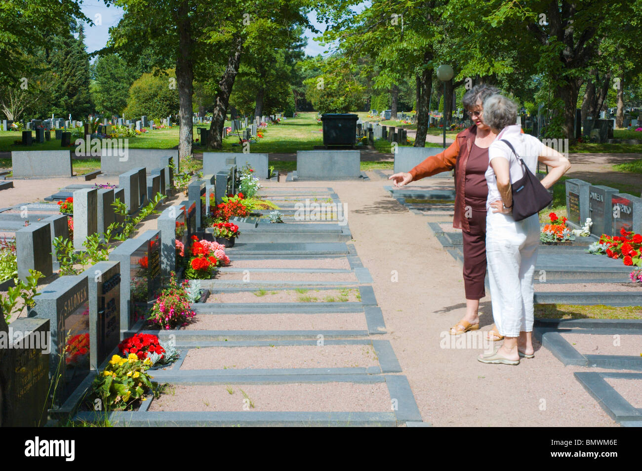 Women in 60s at the main cemetery Pori western Finland Europe - Stock Image