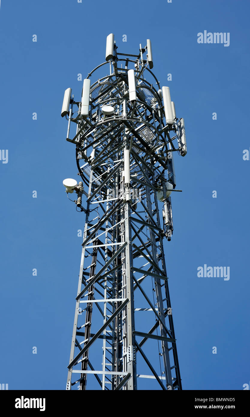 MOBILE PHONE MAST SHOT ON A SUNNY DAY AGAINST A BLUE SKY - Stock Image