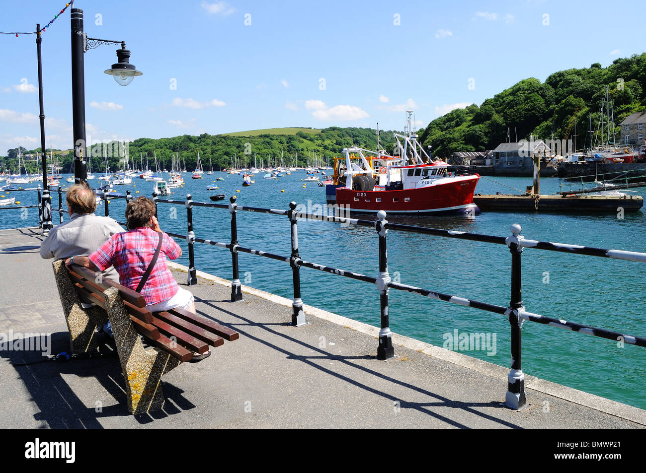 tourists relaxing on the quay at polruan in cornwall, uk - Stock Image