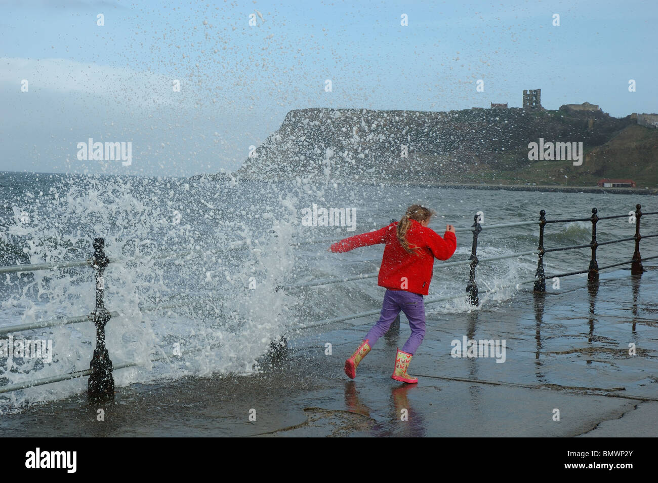 young girl plays daredevil as waves crash over the seafront, Royal Albert Drive, Scarborough, North Yorkshire, England, - Stock Image