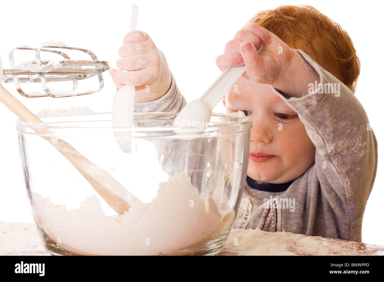 Boy cooking, mixing, and making mess. Isolated on white - Stock Image