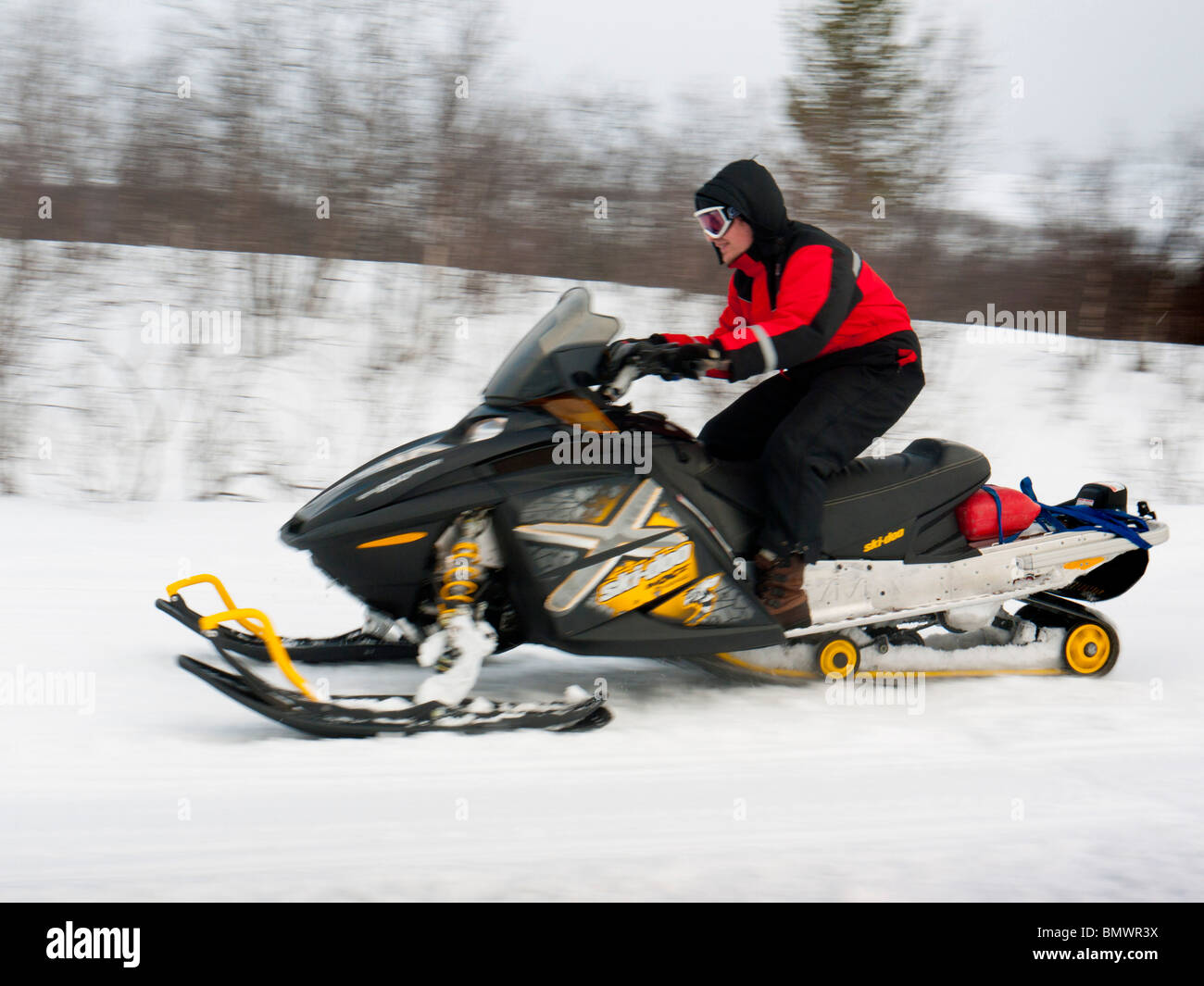 A young man drives a snow mobile through the snow at Kiruna, Lapland, Northern Sweden. - Stock Image
