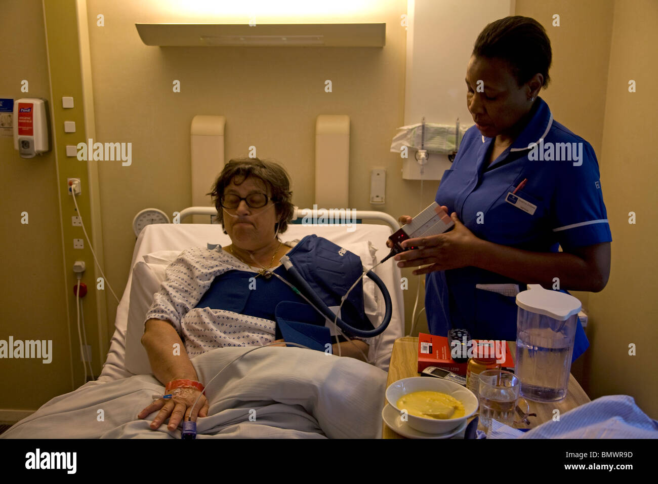 Middle Aged Woman in Hospital Bed Ashtead Surrey England - Stock Image