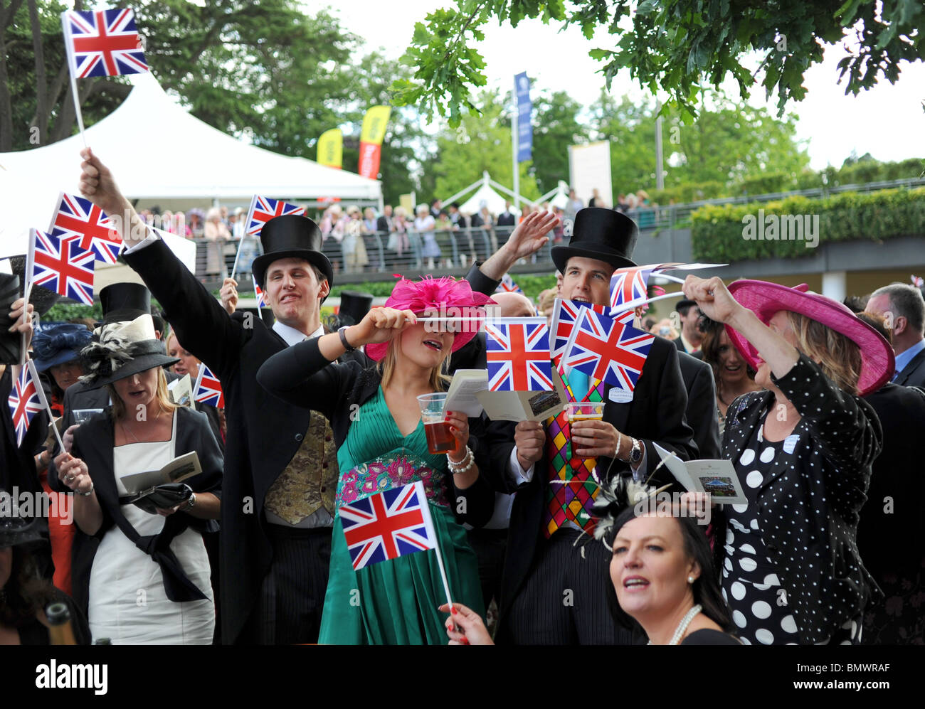 Royal Ascot Berkshire - Racegoers enjoy the traditional end of day singsong at the bandstand with union jack flags - Stock Image