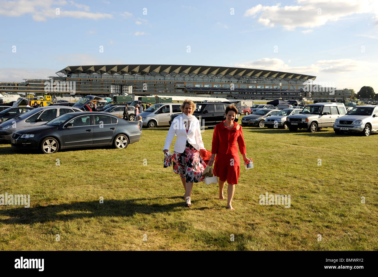 Royal Ascot Berkshire - Female Racegoers walking across the heathland car park in front of Grandstand after days - Stock Image
