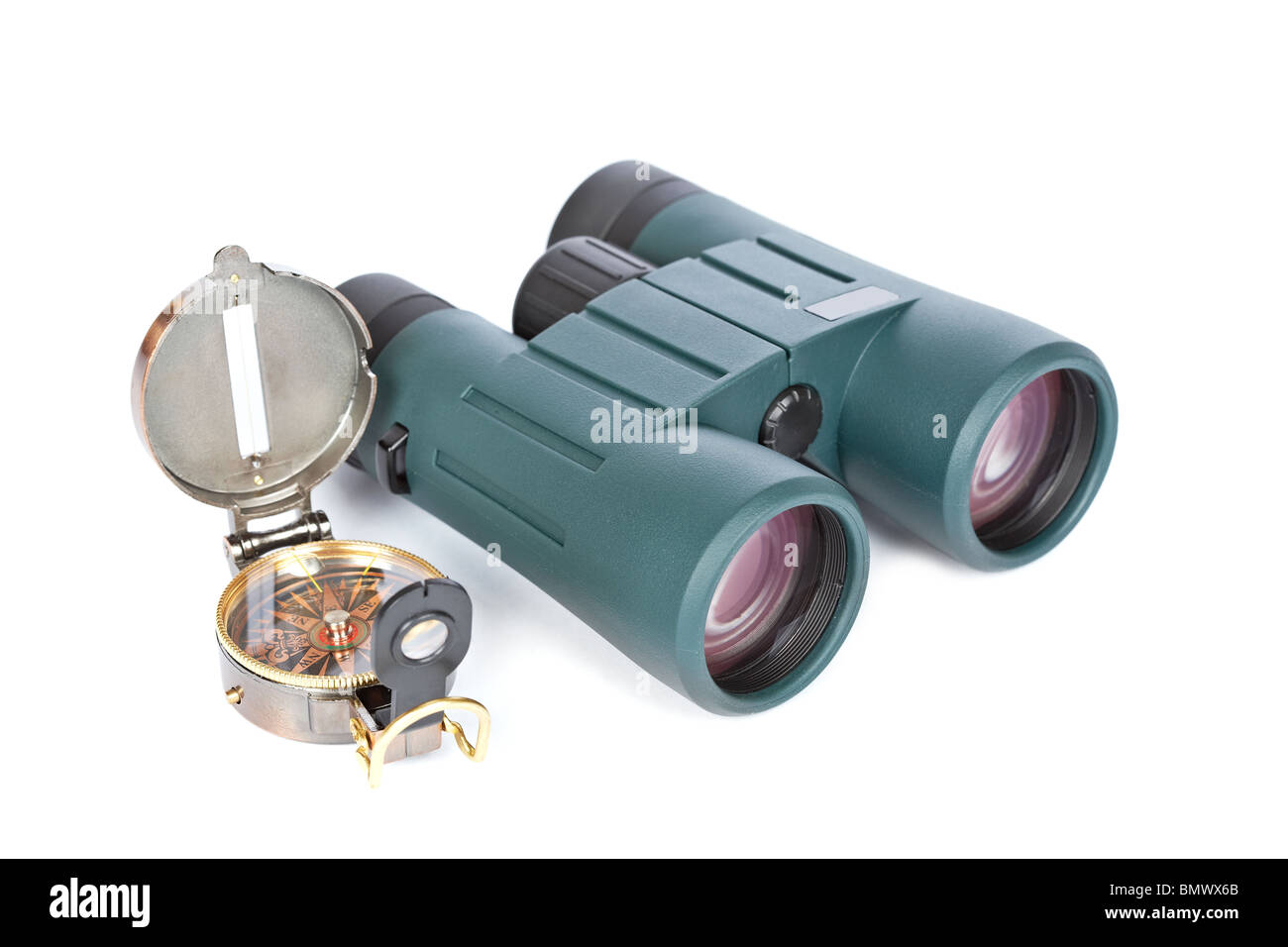Compass and green binoculars on a white background. Shallow depth of field - Stock Image