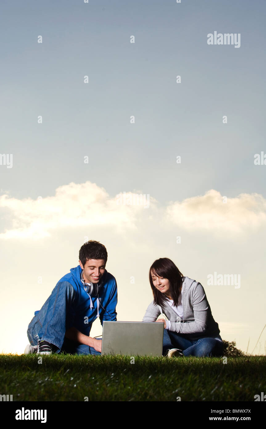young couple using laptop outdoors - Stock Image