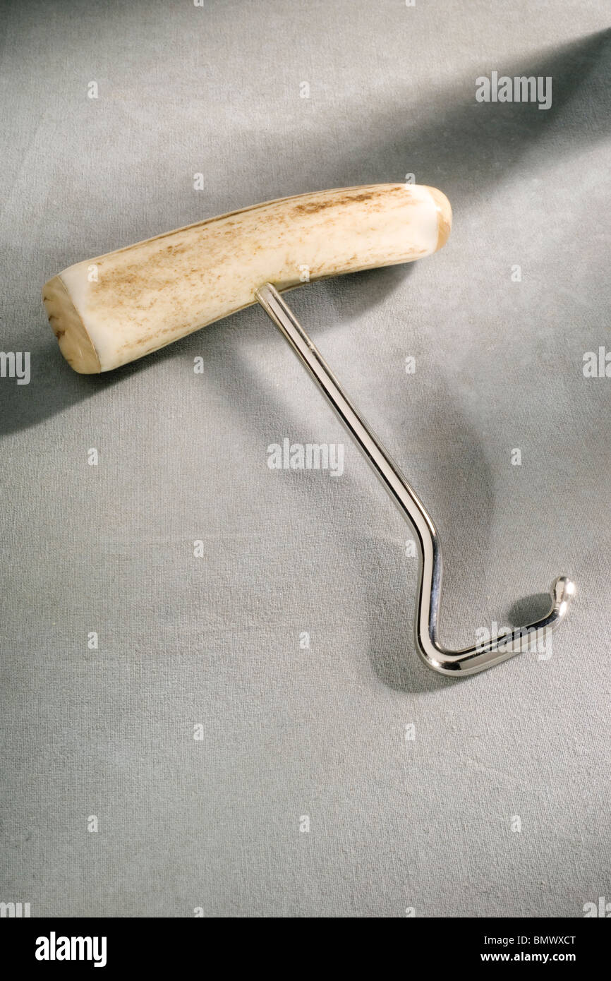 Old Style Bone handled chrome boot hook on Grey backdrop - Stock Image