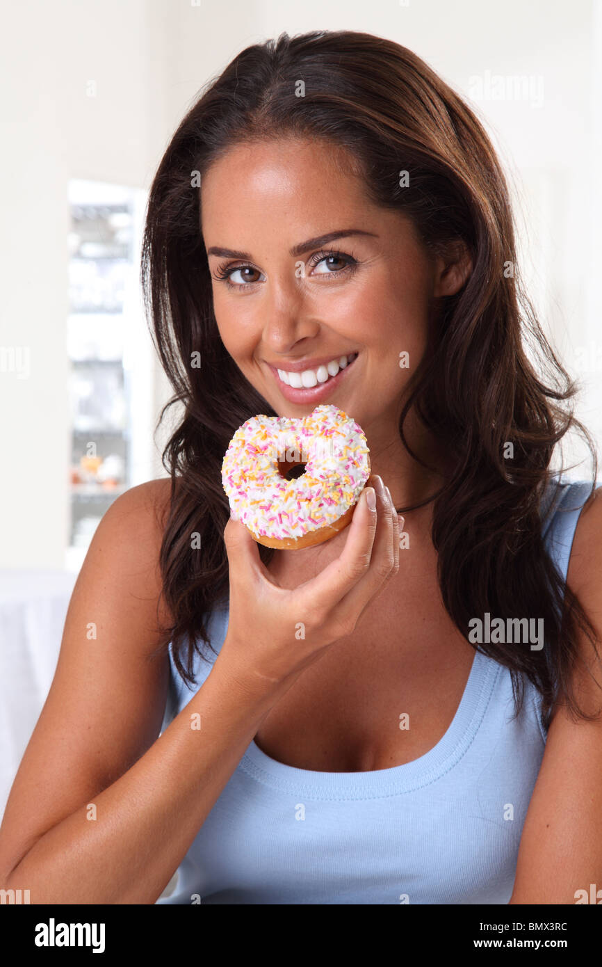 WOMAN EATING DOUGHNUT - Stock Image