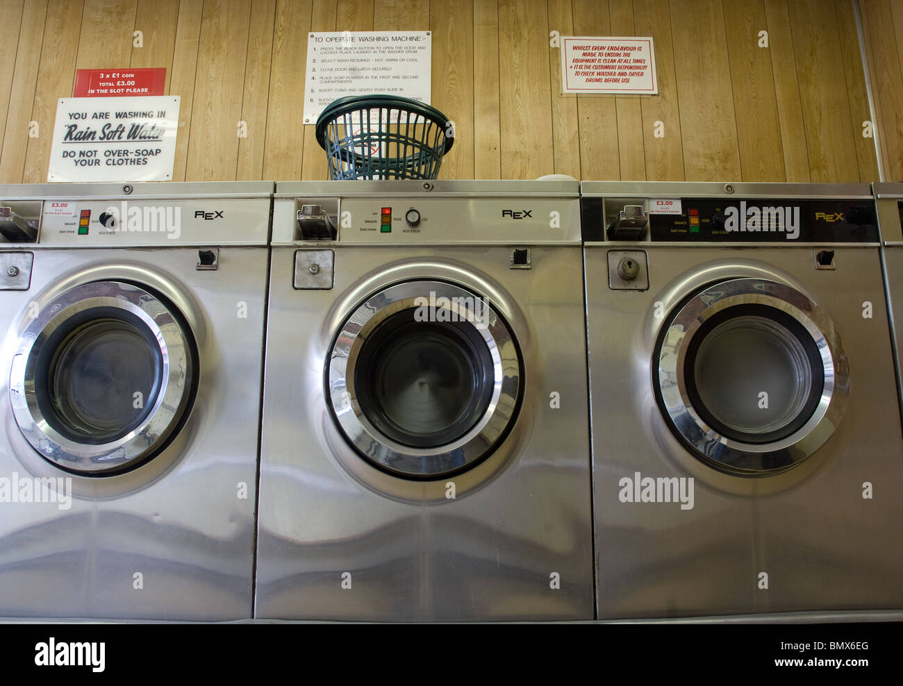 three washing machines inside a public laundrette - Stock Image