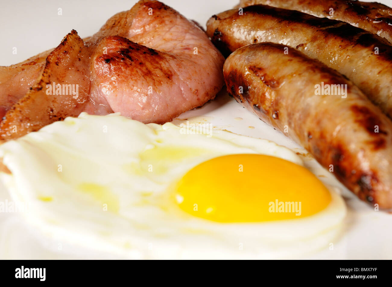 Stock photo of a traditional English Breakfast of sausages, fried eggs and bacon. Cholesterol hell but nice. - Stock Image