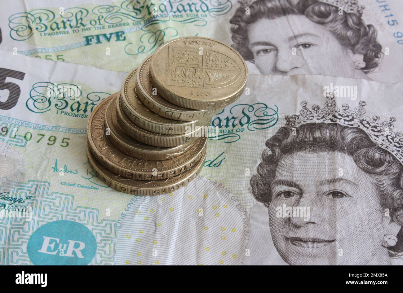 A stash of used, dirty English money consisting of coins and notes - Stock Image