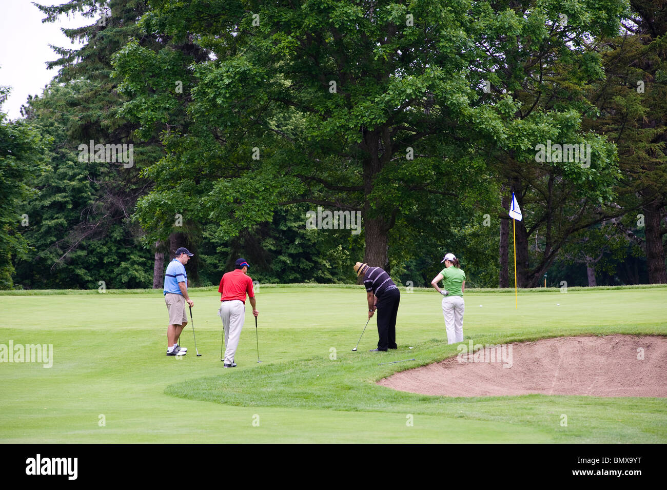 A golfer hits his approach shot onto the green while the  other members of his foursome are watching. - Stock Image