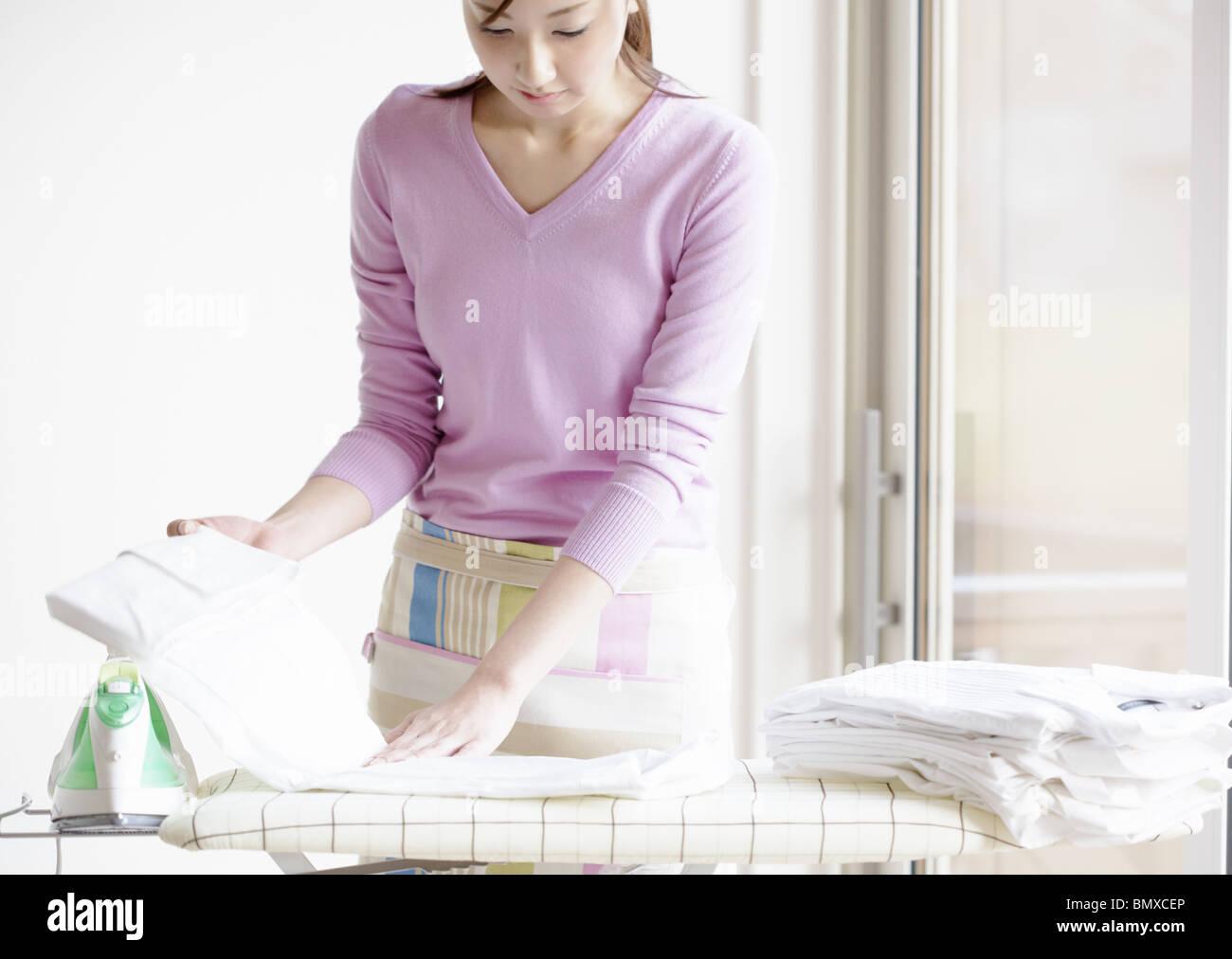 Woman folding shirt - Stock Image