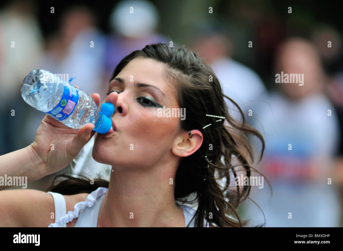 Mass participation running event competitor drinking water, London, United Kingdom - Stock Image