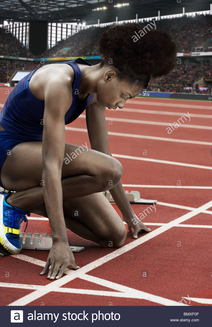 Runner at starting line in stadium - Stock Image