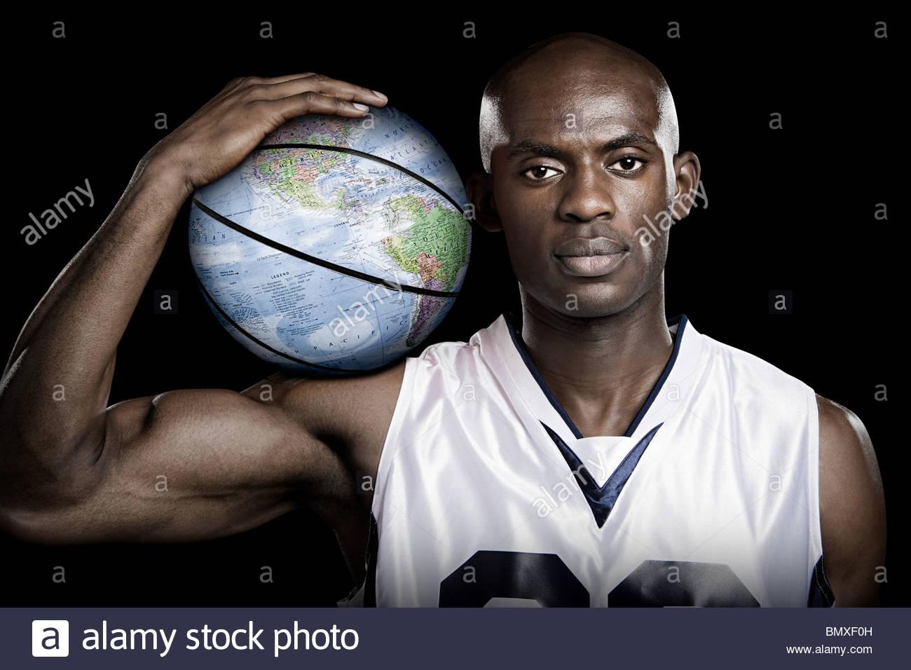 Basketball player with globe basketball - Stock Image