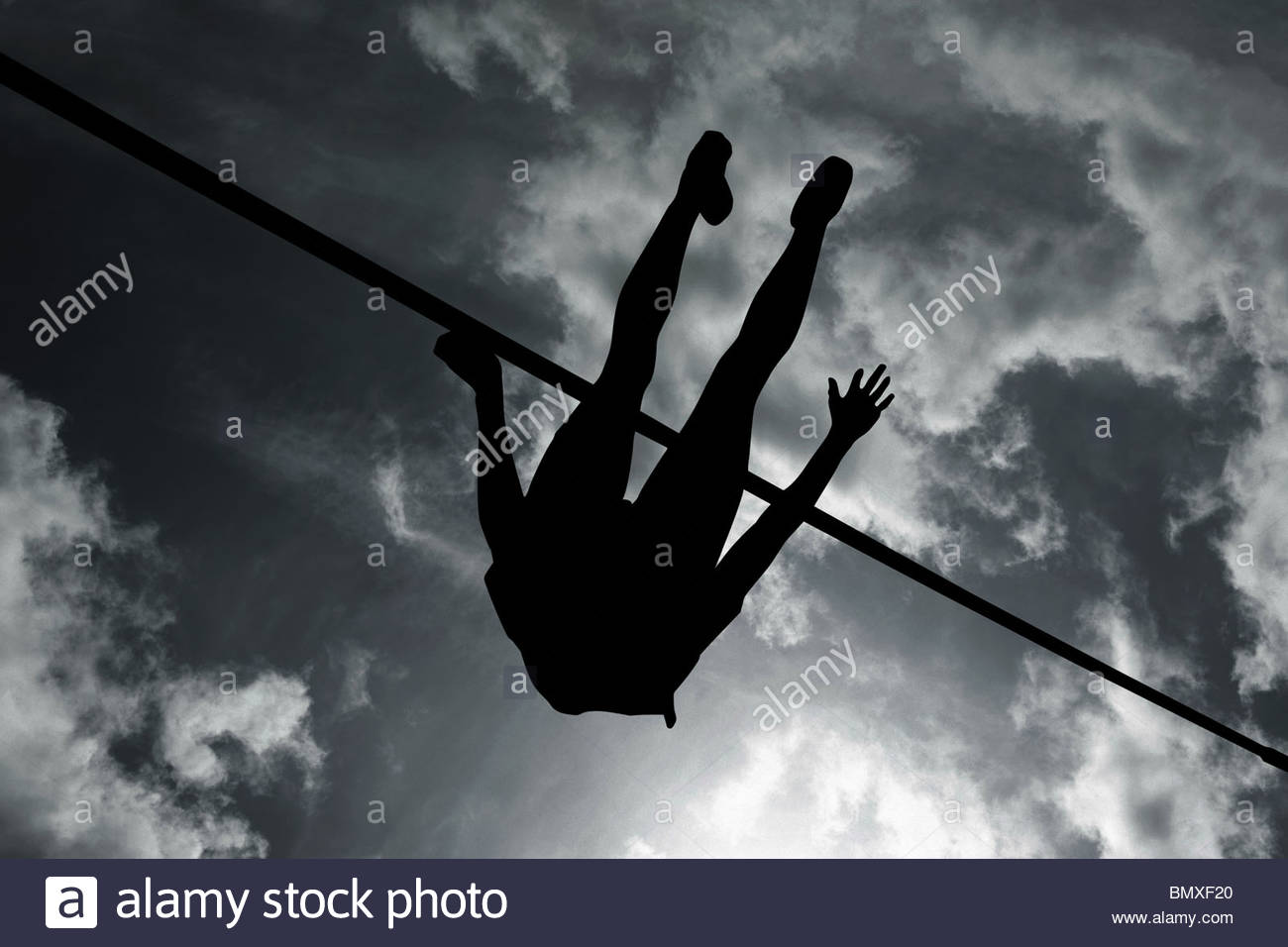 Silhouette of high jumper - Stock Image
