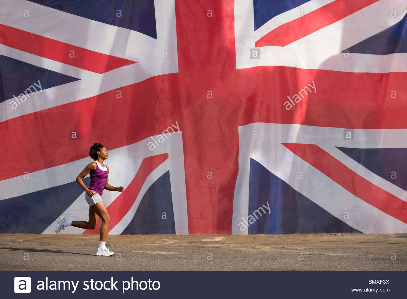 Woman running past british flag - Stock Image